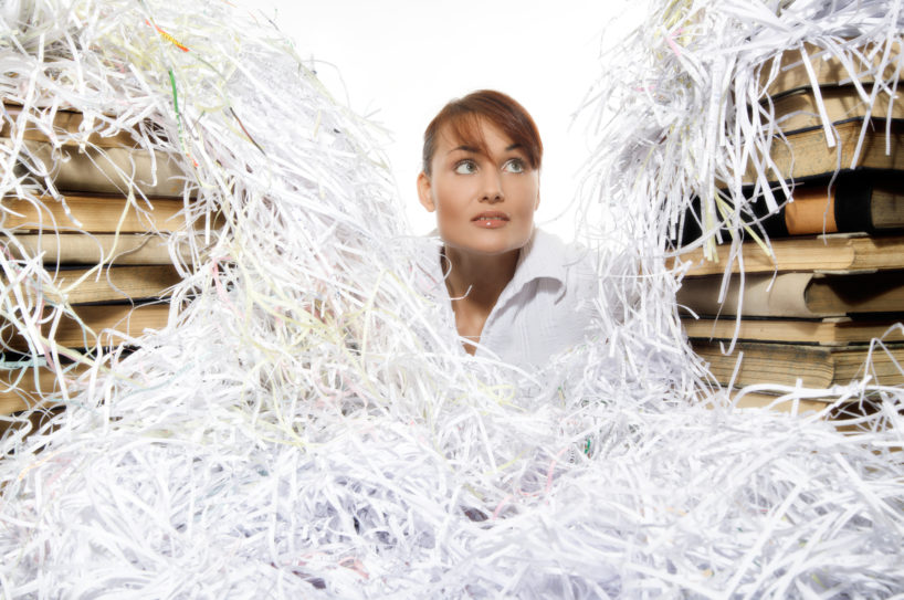 Young woman with shredded paper. Focus on face